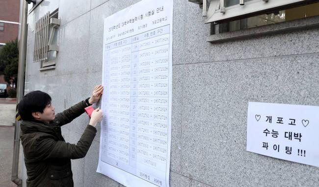 2018학년도 대학수학능력시험을 하루 앞둔 22일 오전 서울 강남구 개포고등학교에서 학교 관계자가 시험실 안내표를 부착하고 있다.(뉴시스)