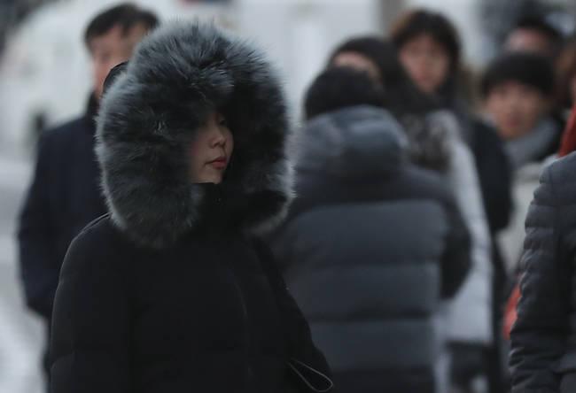 올겨울 들어 가장 강력한 한파가 찾아온 12일 오후 서울 중구 한 버스정류장에서 시민들이 추위를 피하며 버스를 기다리고 있다.(뉴시스)