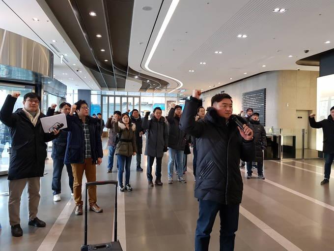 12일 오후 기자회견이 열리기 전 YTN 사옥 로비 안에서 최남수 사장 사퇴를 위한 구호를 외치는 언론노조 YTN지부 조합원들. 오른쪽 앞에는 박진수 YTN지부장의 모습이 보인다.