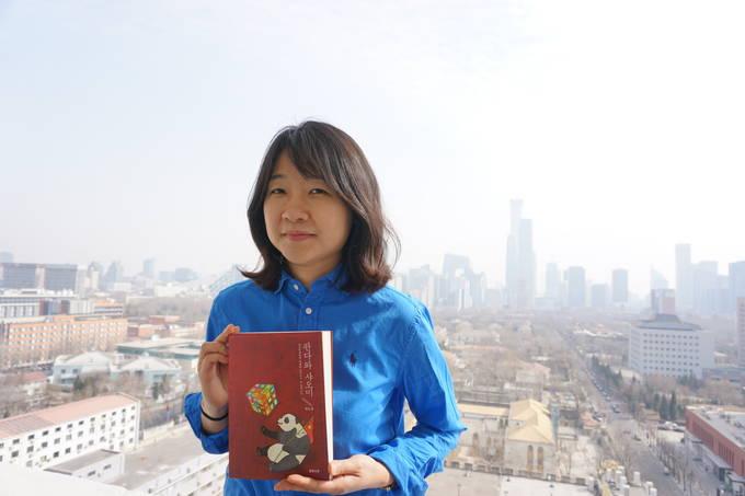박은경 경향신문 기자(베이징 특파원)가 지난 5일 베이징 시내 외교공관이 밀집한 젠궈먼(建國門) 한 건물에서 책을 들고 포즈를 취한 모습. 뒤로 CCTV 사옥을 비롯해 베이징 시가지가 보인다.(박은경 기자 제공)